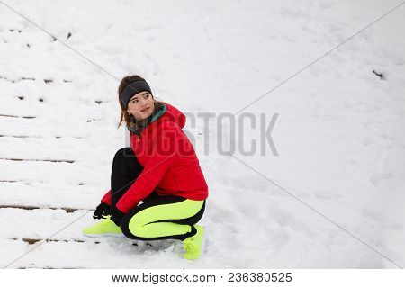 Winter Sports Fashion Concept. Woman Tying Sport Fitness Shoes In Snow, Footwear For Workout Outside