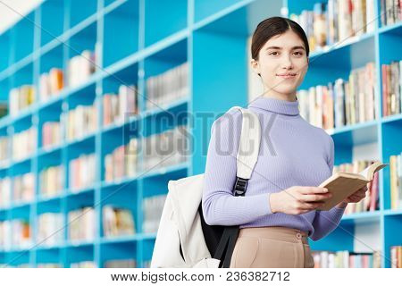 Clever teenage girl with backpack looking at camera while standing by bookshelf in college library
