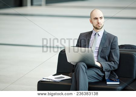 Elegant businessman in formalwear sitting on black sofa in airport lounge and looking through window