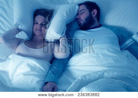 Man Snoring And Woman Can't Sleep, Covering Ears With Pillow For Snore Noise