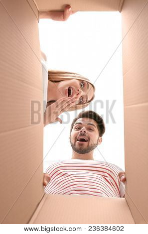 Young couple unpacking parcel at home, view from inside of box