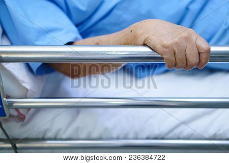Asian Senior Or Elderly Old Woman Patient Lie Down Handle The Rail Bed With Hope On A Bed In The Hos
