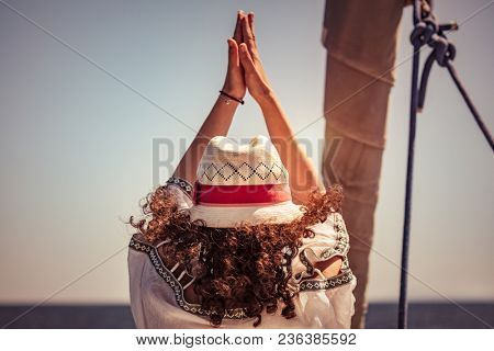Woman doing yoga exercises, rear view of a female standing in yoga asana on the sailboat among sea, cleansing of aura, meditating on vacation, happy healthy summer holidays