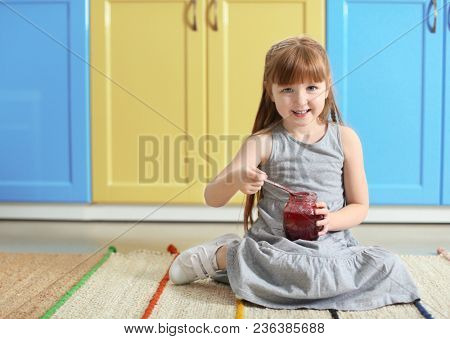Cute little girl with jar of jam at home