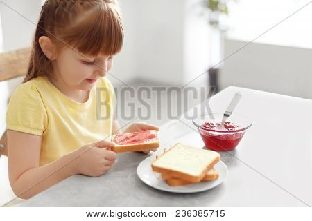 Cute little girl holding toast with jam at home