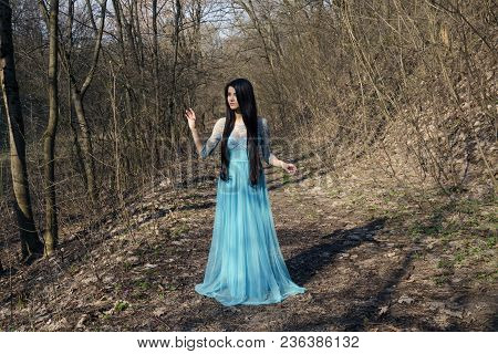 Girl With Long, Beautiful Hair In Blue Length Dress Against Forest Background, Spring Warm Day