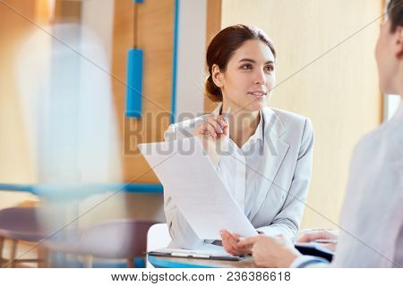 Young confident lawyer with paper consulting her client or discussing document with colleague at meeting