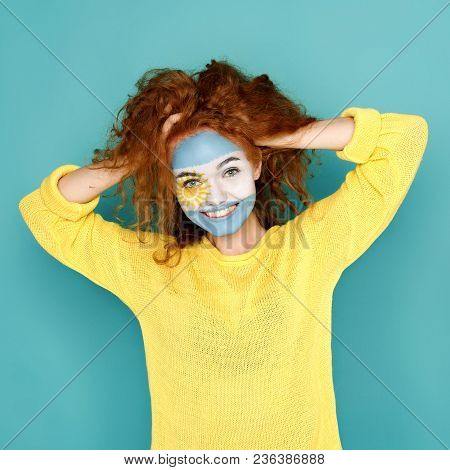 Portrait Of Happy Woman With The Flag Of Argentina Painted On Her Face. Football Or Soccer Team Fan,