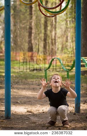 Portrait Of Cute Kid Boy Jumping On The Climbing Frame. Young Boy Climbing On Playground During Summ