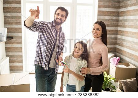 Beautiful Family Is Standing Together In Their New Apartment. Man Is Looking Straight And Pointing.