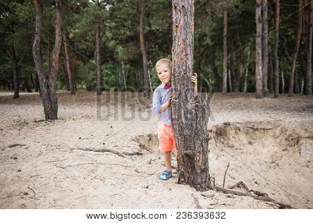 Portrait Of Cute Stylish Funny Little Caucasian Boy Outdoors. Shy Smiling Handsome Blonde Boy Hides