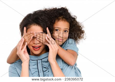 Daughter Covering Eyes Of Surprised Mother With Hands Isolated On White