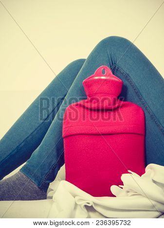 Warming Up During Cold Winter Or Autumn Days. Woman Lying On Couch With Hot Water Bottle, Legs Shot