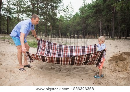 Young Healthy White People Arranging Place For Family Picnic On Sandy Beach Near Wood On Summer Week