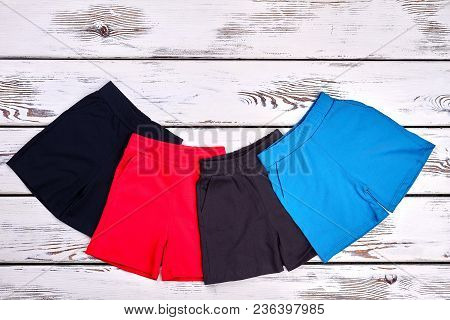 Set Of Kids Colored Cotton Shorts. Collection Of New Brand Shorts For Childrens On White Wooden Back