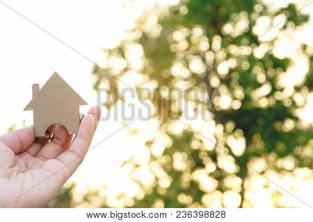 Hand Holding Paper House Model On Bokeh Background. Home Loan For New Family. Loan For Real Estate C