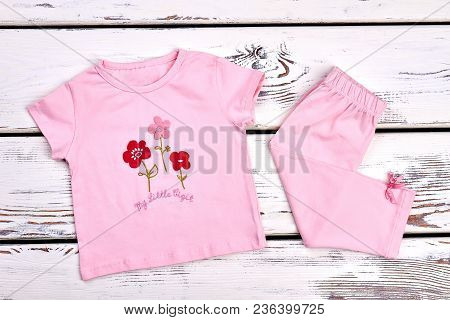 Toddler Girl Pink Color Apparel. Little Girl Beautiful Cotton T-shirt And Pink Capri On White Wooden