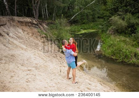 Young Healthy White Family Has Fun Outdoors On Summer Weekend. Positive Smiling Woman And Man Enjoyi
