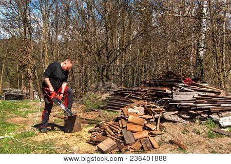 Man Cutting With Electric Chain Saw. Work On The Farm. Wood Preparation For Heating. The Woodcutter