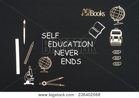 Concept back to school, text self education never ends with school supplies chipboard miniatures placed on blackboard poster