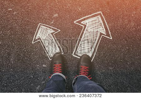 Sneakers On The Asphalt Road With Drawn Arrows Pointing In Two Directions. Making Decisions And Maki