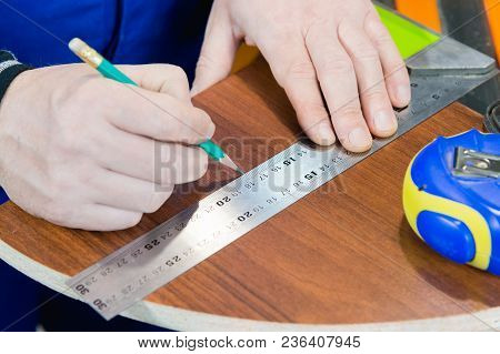 Close-up Men's Hands Draw A Pencil On The Ruler With A Sub-standard Template For Cutting Out Furnitu