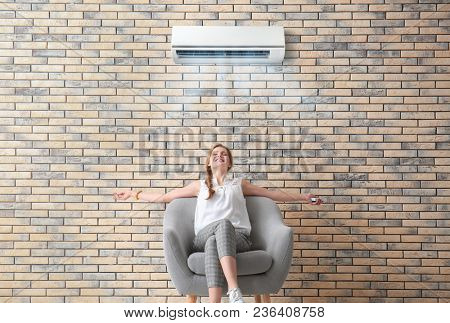 Young woman sitting in armchair and enjoying cool air flow from conditioner indoors