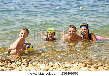 Dad And His Little Children Are Swimming In The Sea