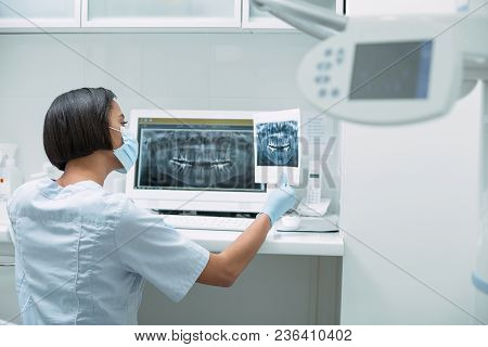 My Modern Device. Professional Dark-haired Dentist Holding An Image And Working On Her Advanced Devi