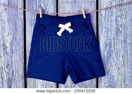 Clothesline With Hanging Kids Shorts. Childs Blue Shorts Drying On Rope On Grey Wooden Background.