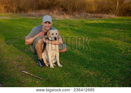 Young Guy With Labrador On Walk In Summer Park. Educating Dog. Play With A Pet. Dog Handler.