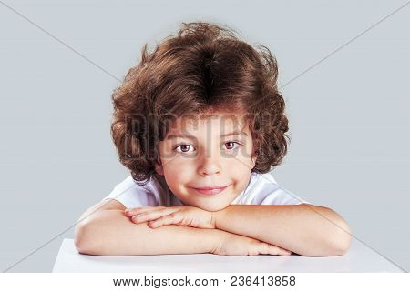 Closeup Of Adorable Little Boy On The Table Edge, Smiling, Head On Crossed Hands. Adorable Child Iso