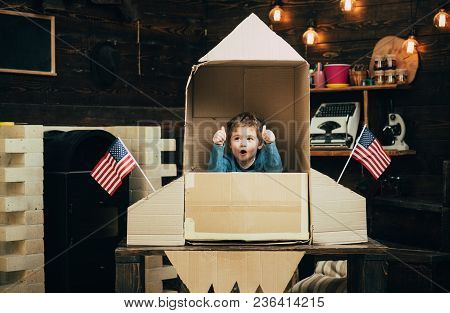 Boy Play With Rocket, Cosmonaut Sit In Usa Rocket Made Out Of Cardboard Box. Kid Excited Sit In Card