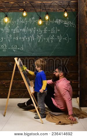 Little Genius Learning Math. Teacher Or Father Helping Kid To Solve Equation On Chalkboard. Bearded