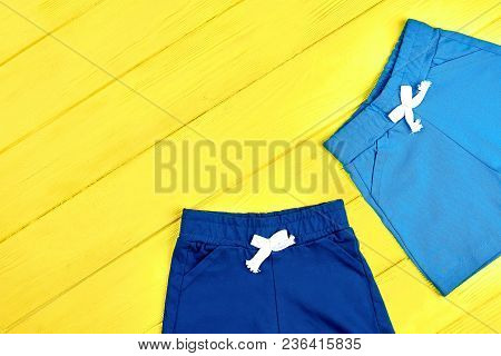 Kids Casual Shorts, Copy Space. Toddler Childs Colored Short Pants On Yellow Summer Background, Top