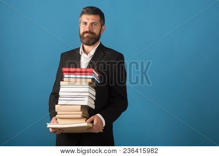 Businessman With Pile Of Books On Blue Background. Literature Lesson And Reading Book. School Time O