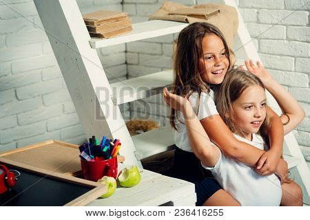 Happy Smiling Girls Are Going To School For The First Time. Kids Indoors Of The Class Room. Back To