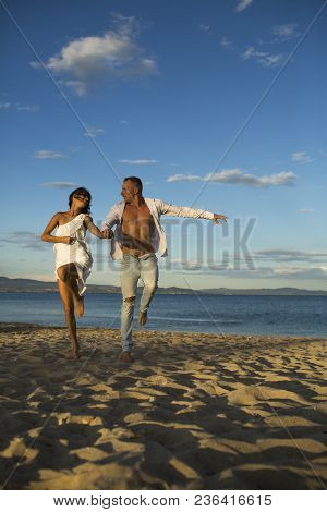 Man And Woman Hold Hands, Couple Happy On Vacation. Couple In Love Stand On Beach, Seashore. Couple