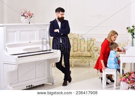 Home Schooling Concept. Parents Enjoying Parenthood, Happy. Father Stands Near Piano, Watching While