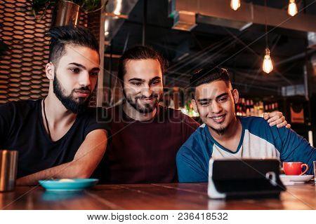 Group Of Arabian Friends Taking Selfie In Lounge Bar. Mixed Race Young Men Having Fun In Loft Cafe.