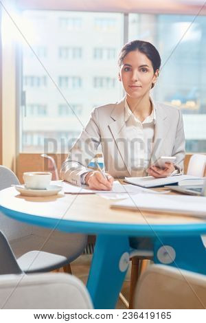 Young confident businesswoman organizing her work while working by table in cafe