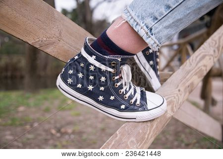 Teenage Legs Wearing Denim Sneakers Sneakers Of Daisies, Standing On A Fence In A Park. Street Hipst
