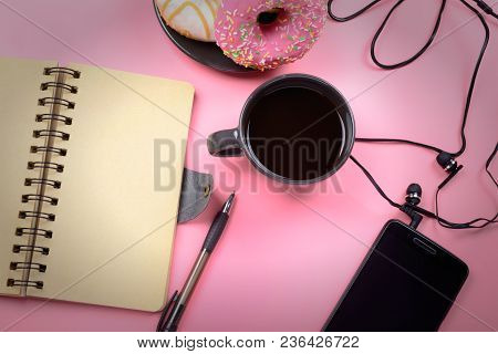 A Cup Of Coffee, A Notebook With Brown Pages, A Pen And A Phone With Headphones Lie On A Bright Pink