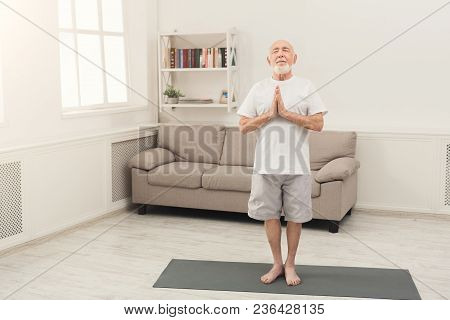 Meditating Senior Man With Praying Hands. Serene Elderly Guy Practicing Yoga And Relaxing At Home. A