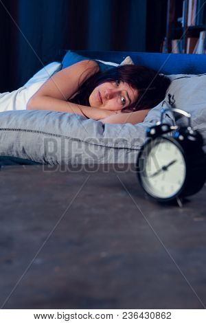 Photo of dissatisfied woman with insomnia lying on bed next to alarm clock at night