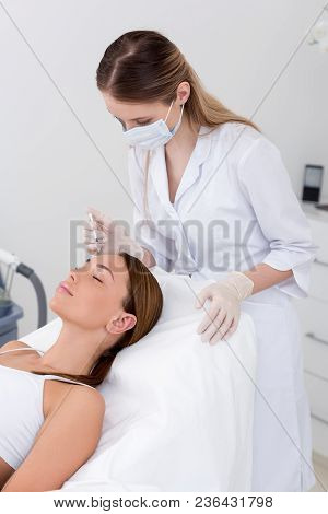 Young Woman Getting Beauty Injection Made By Cosmetologist In Salon