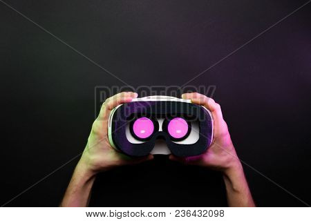 Photo of hands holding virtual reality glasses with burning pink light on black background