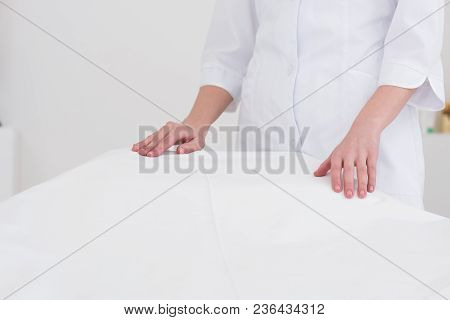 Partial View Of Cosmetologist In White Coat Standing Near Empty Massage Table In Salon