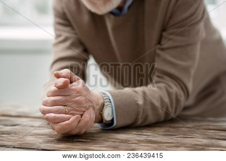 Sad Feelings. Nice Aged Man Putting His Hands On The Table While Being All Alone