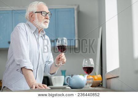 Lonely Evening. Sad Elderly Man Holding A Glass Of Wine While Looking Into The Window